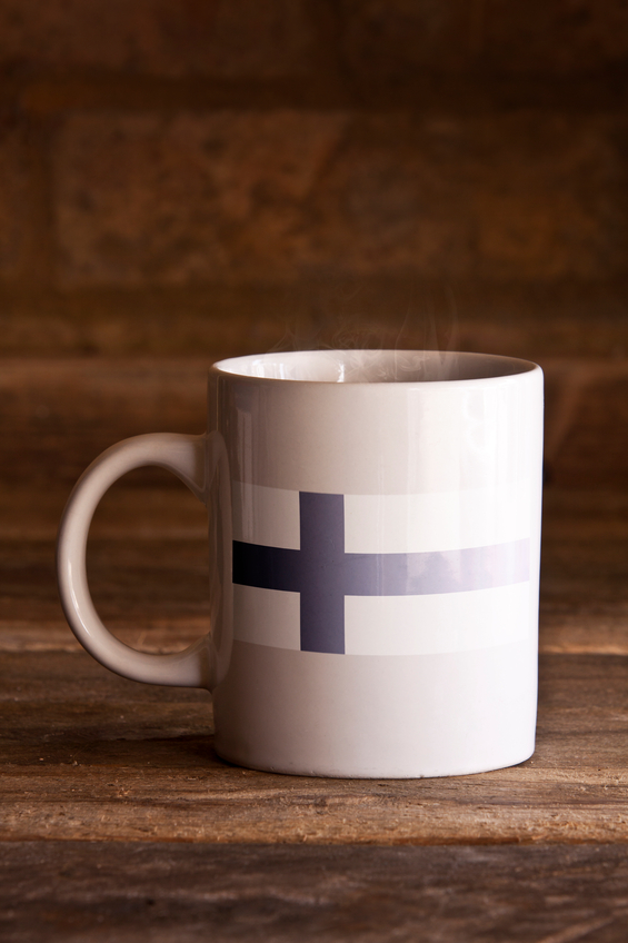 A macro shot of a white ceramic mug with a stenciled flag on the front, shot using natural daylight, on a wooden surface.