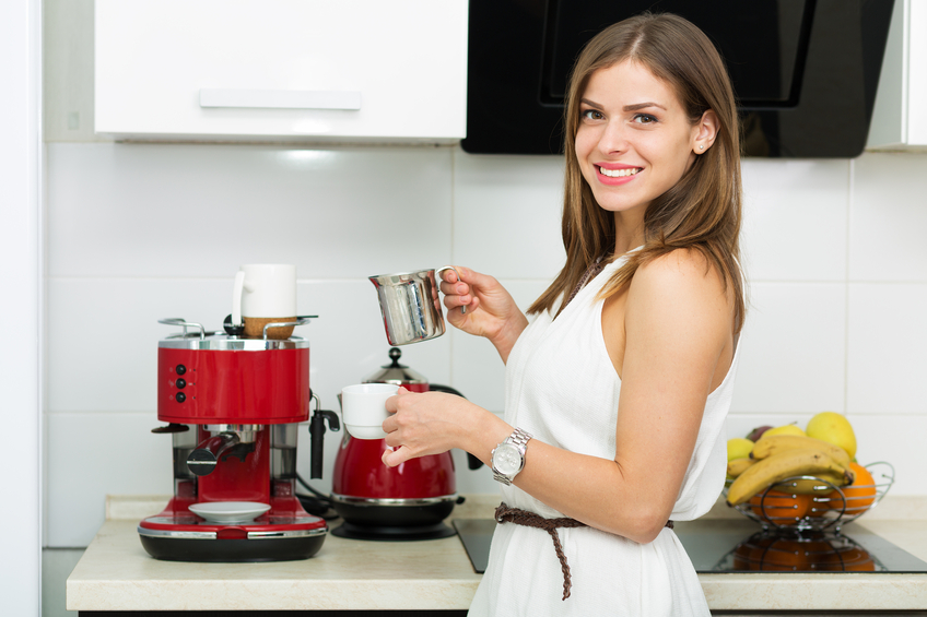 Beautiful woman making coffee for breakfast in the kitchen
